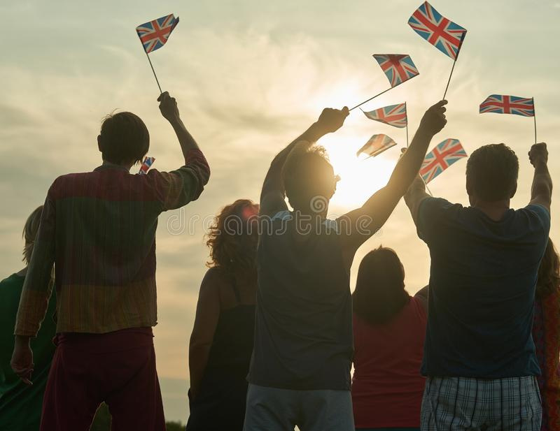 Back view, silhouette of british people with flags. Patriotic british family, rear view stock images