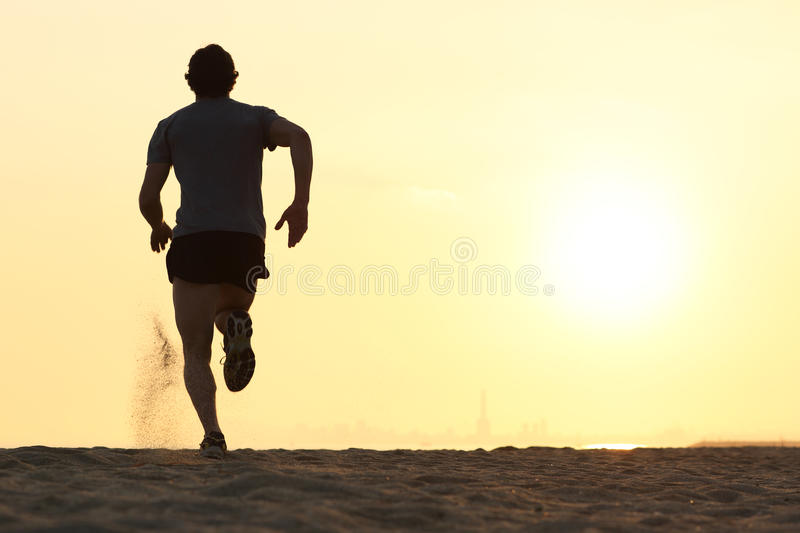 Back view silhouette of a runner man running on the beach stock images