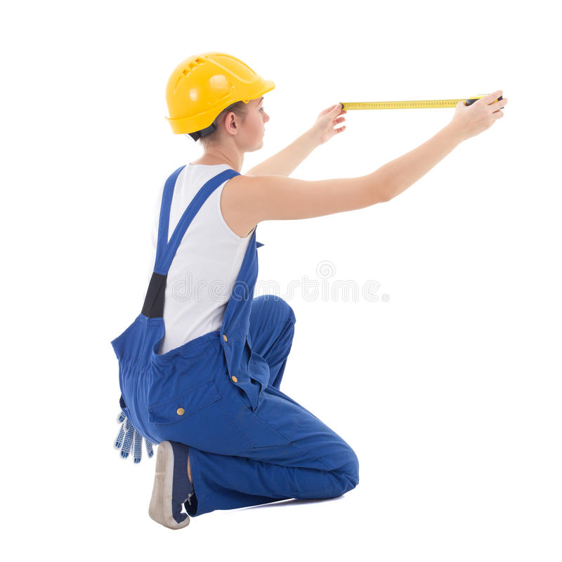 back view of sitting woman builder in workwear measuring something with measure tape isolated on white stock images