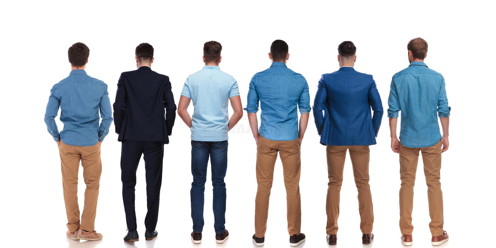 Back view of six relaxed young men standing. Back view of six relaxed young men wearing suits and blue shirts standing on white background with hands in pockets royalty free stock photo