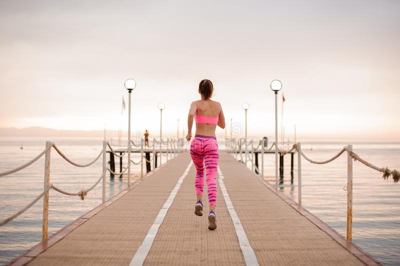Back view of slim and young girl running over the wooden bridge royalty free stock photos
