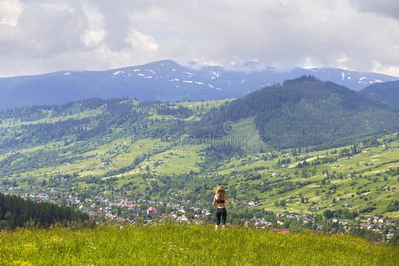 Back view of slim young woman standing on grassy valley on background of green mountains on sunny summer day royalty free stock photography