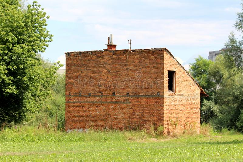 Back view of small abandoned red brick family house with broken missing windows and disconnected electrical wires. Surrounded with uncut grass and tall trees on stock photos