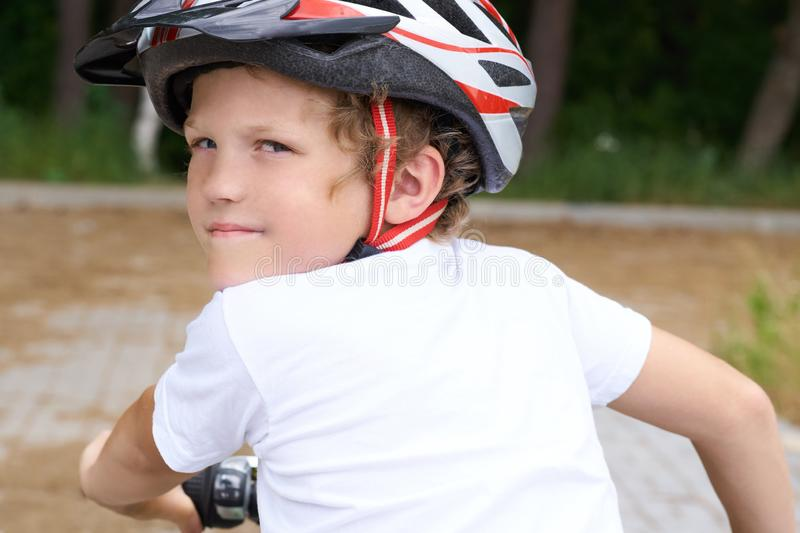Back view of small boy in protective helmet riding bicycle in park on summer day. Weekend activity. Back view of small boy in protective helmet riding bicycle royalty free stock image