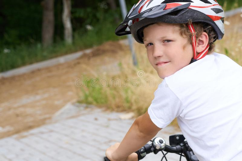 Back view of small boy in protective helmet riding bicycle in park on summer day. Weekend activity. Back view of small boy in protective helmet riding bicycle stock photos