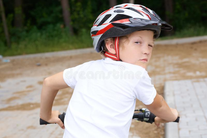 Back view of small boy in protective helmet riding bicycle in park on summer day. Weekend activity. Back view of small boy in protective helmet riding bicycle royalty free stock photos