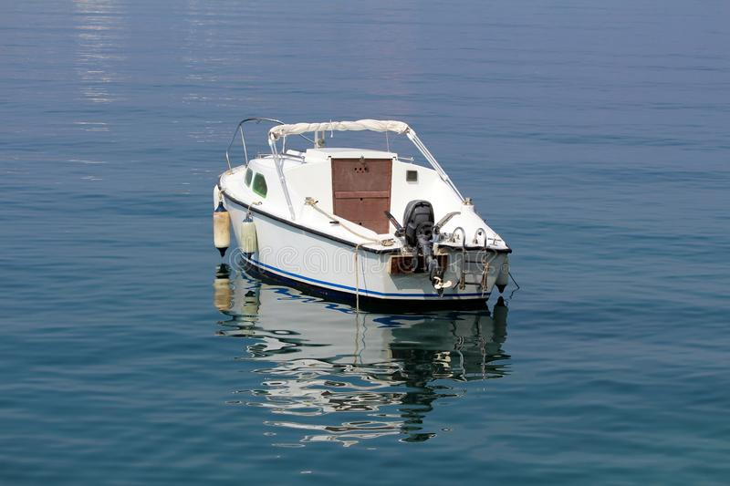 Back view of small white boat with outboard boat motor anchored in local harbor surrounded with calm clear blue sea. On warm sunny summer day royalty free stock photography