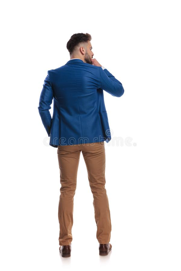 Back view of smart guy thinking with hand at chin stock photography