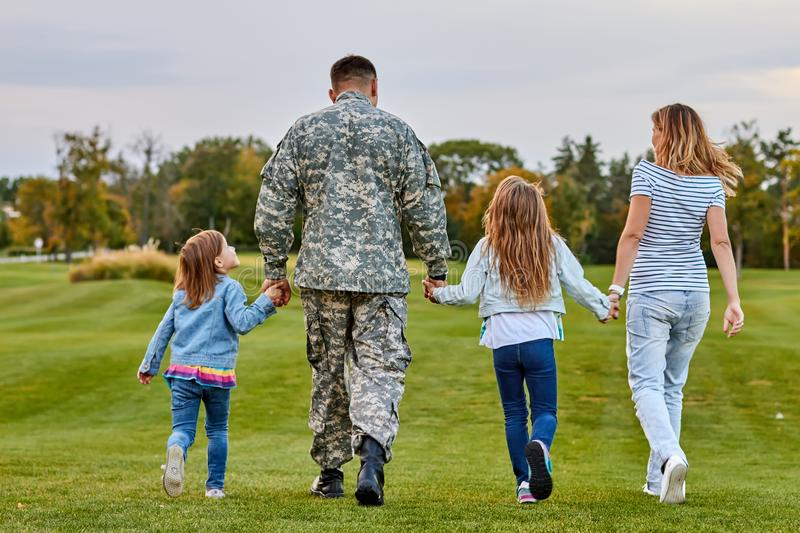 Back view soldier`s family walking. stock photos