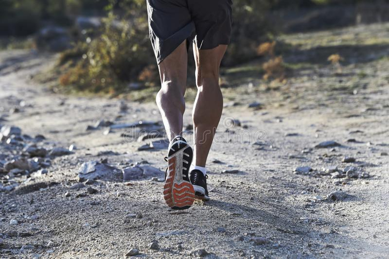 Sport man with ripped athletic and muscular legs running off road in jogging training workout at countryside in Autumn background stock photography