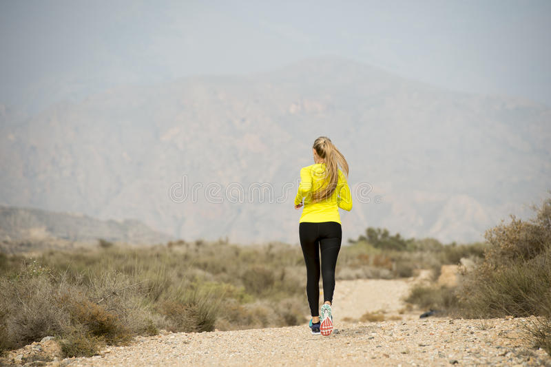 Back view sport runner girl training on earth trail dirty road desert mountain landscape royalty free stock photo