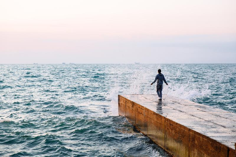 Back view on sportsman jumping with skipping rope, on pier. Full length view of young man in sportswear jumping with skipping rope, workout on pier, near the sea royalty free stock images