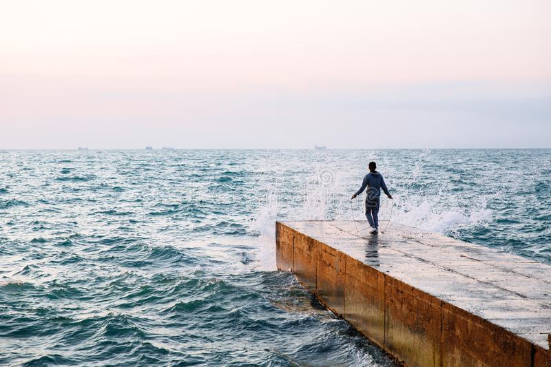 Back view on sportsman jumping with skipping rope, on pier. Full length view of young man in sportswear jumping with skipping rope, workout on pier, near the sea royalty free stock photography