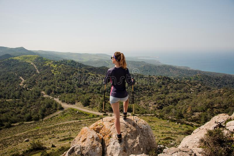Back view sporty girl standing on the rock in shorts with walking sticks stock photography