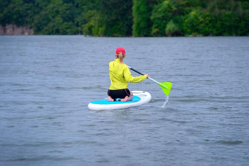 Back view of a sporty girl with white hair sitting on a board with a paddle on the river stock photo