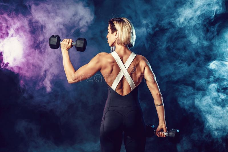 Back view of a sporty woman in fashionable sportswear does the exercises with dumbbells. Photo of muscular woman on dark royalty free stock photography