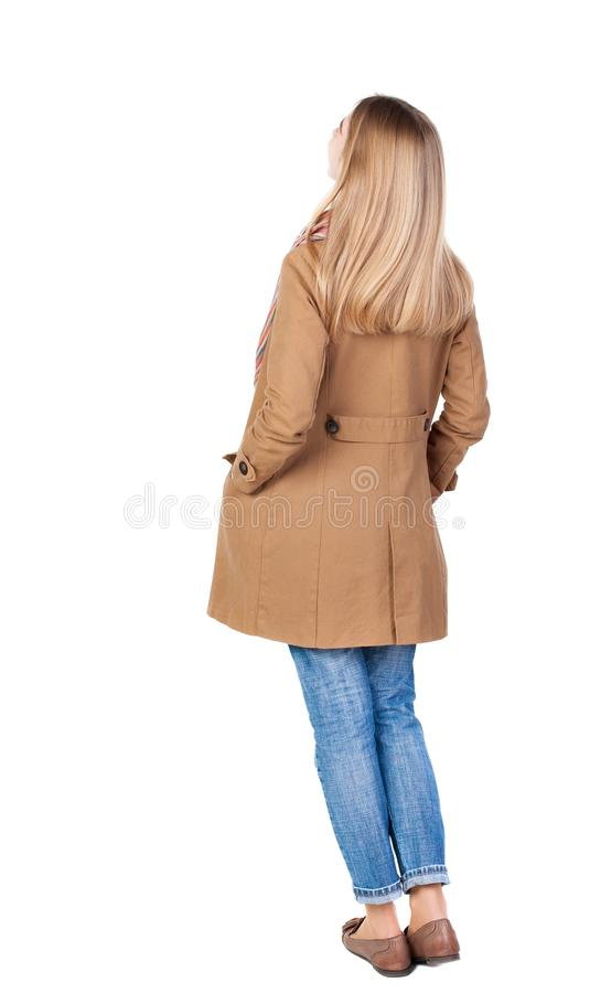 Back view of standing young beautiful blonde woman in brown clo royalty free stock photo
