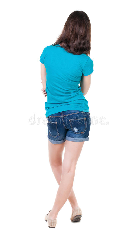 Back view of standing young beautiful brunette woman in shorts. Girl watching. Rear view people collection. backside view of person. Isolated over white stock photography