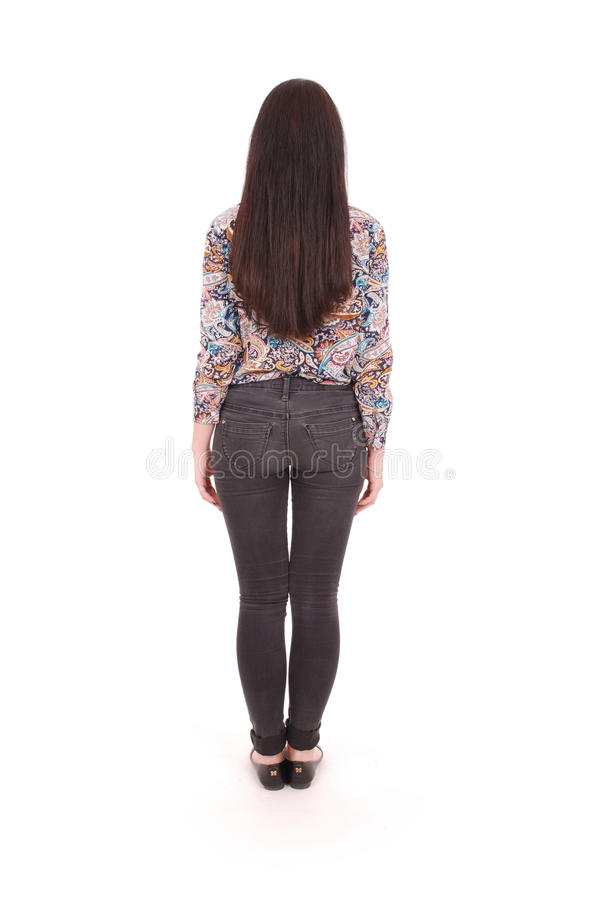 Back view of standing young beautiful woman in jeans. girl watching. royalty free stock images
