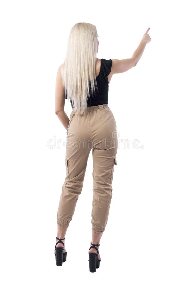 Back view of straight hair stylish blonde woman pointing finger up using touch screen. Full body isolated on white background stock image