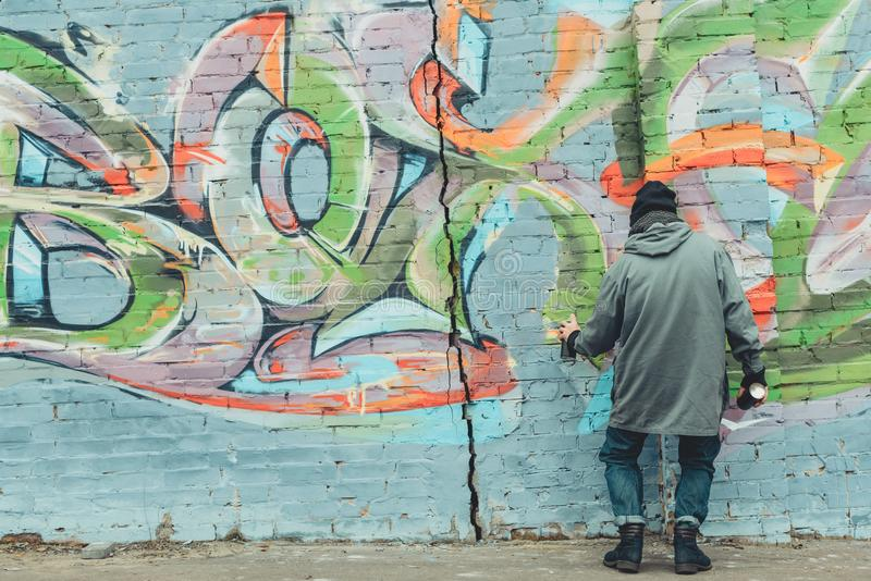 Back view of street artist painting colorful graffiti. On wall royalty free stock image