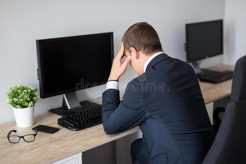 Back view of stressed business man in office - blank pc screen with copy space royalty free stock photography