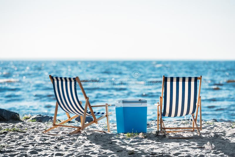Back view of striped chaise lounges and cooler n. Sandy beach stock images