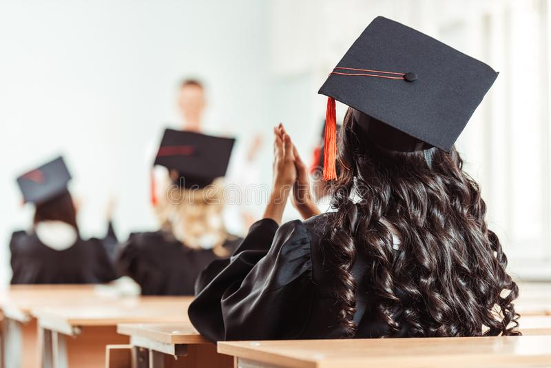 Back view of student girl in graduation costume clapping hands while sitting. At class stock images