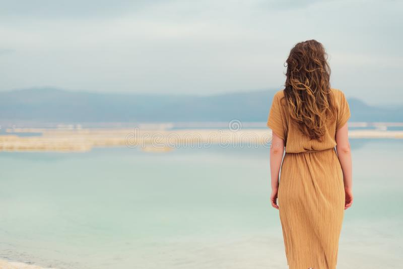 Back view of stylish girl wearing dress on seaside, Dead Sea beach. Travel, summer vacation, holiday, freedom concept. Digital. Detox. Sea background with copy royalty free stock photography