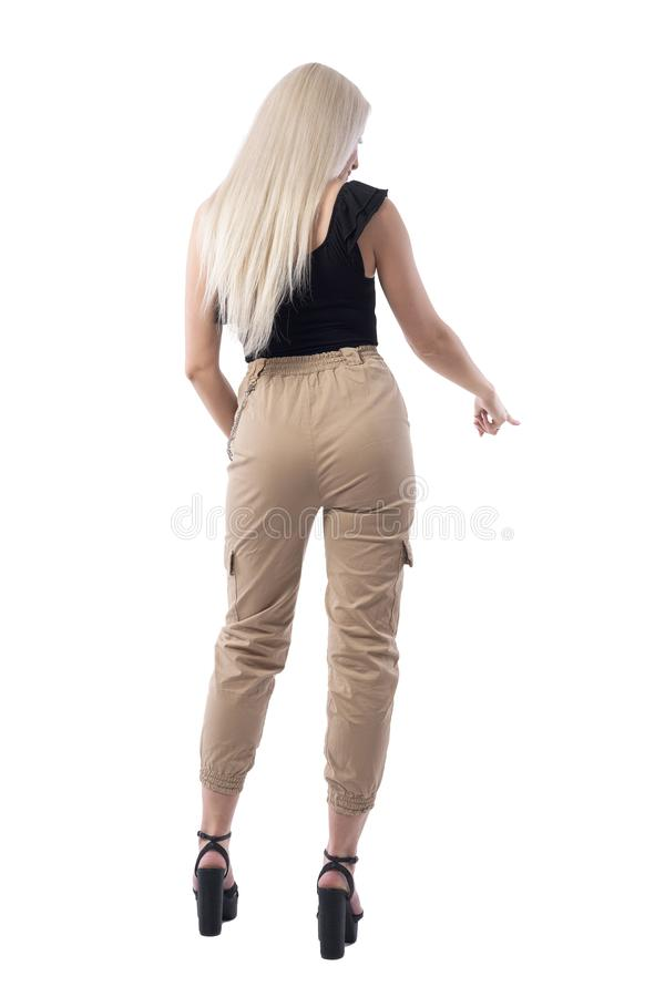 Back view of stylish young blonde beauty woman pointing finger down choosing or selecting something. stock photo