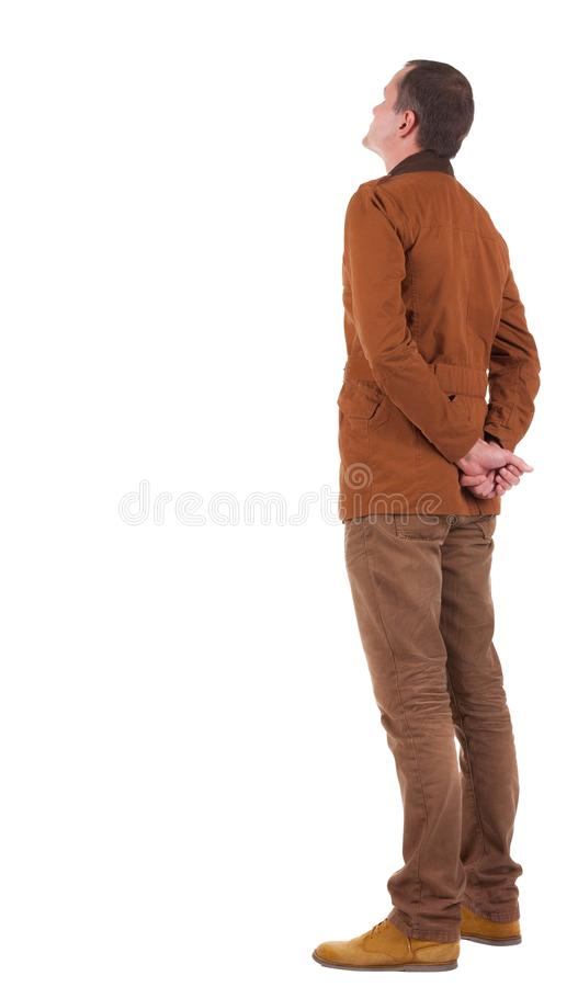 Free Back View Stylishly Dressed Man In A Brown Jacket Looking Up. Royalty Free Stock Image - 76913136