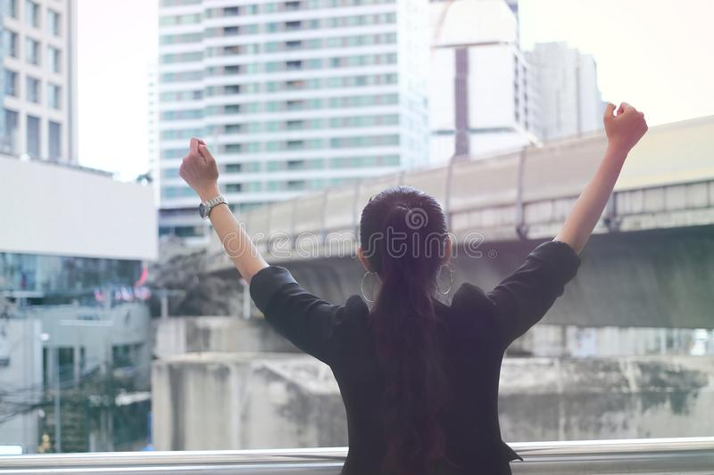 Back view of successful young Asian business woman raising hands with modern city background. stock photo