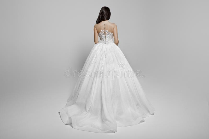 Back view of a superbe brunette female model in a white princess wedding dress,  on a white background. stock images