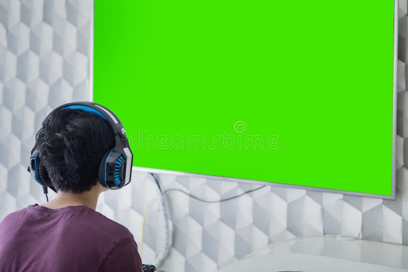 Back view of teen boy plays video game on a TV stock image