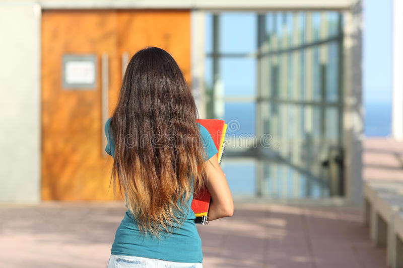 Back view of a teen girl walking towards the school stock images