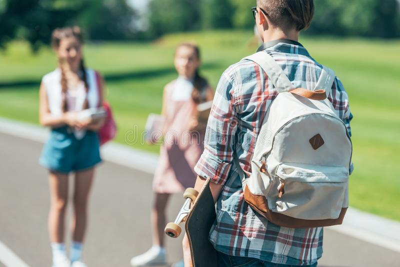 back view of teenage boy with backpack holding skateboard and looking at friends stock photos