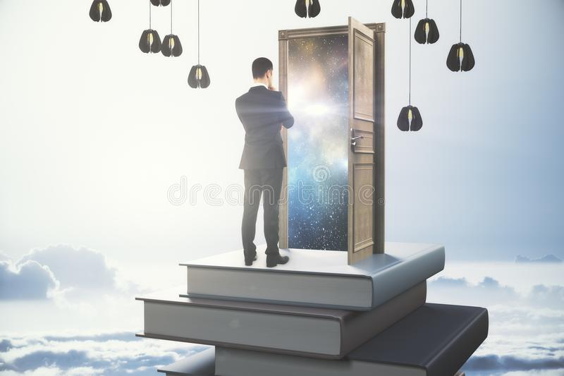 Leadership concept. Back view of thoughtful young businessman standing on abstract book tower with open door on sky background. Leadership concept. 3D Rendering royalty free illustration