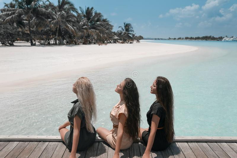 Back view of Three girls sitting on wooden planks on tropical beach Maldives. Girlfriends  having fun, pleasure and enjoyment. stock photo