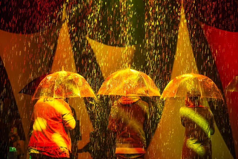 Back view three persons with umbrellas under artificial rain coming from the ceiling and illuminated by colored lights. Unusual stock photos