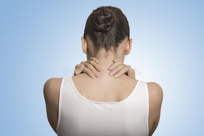 Back view tired female massaging her painful neck. Back and spine disease. Closeup back view tired female massaging her painful neck isolated on blue background stock photography