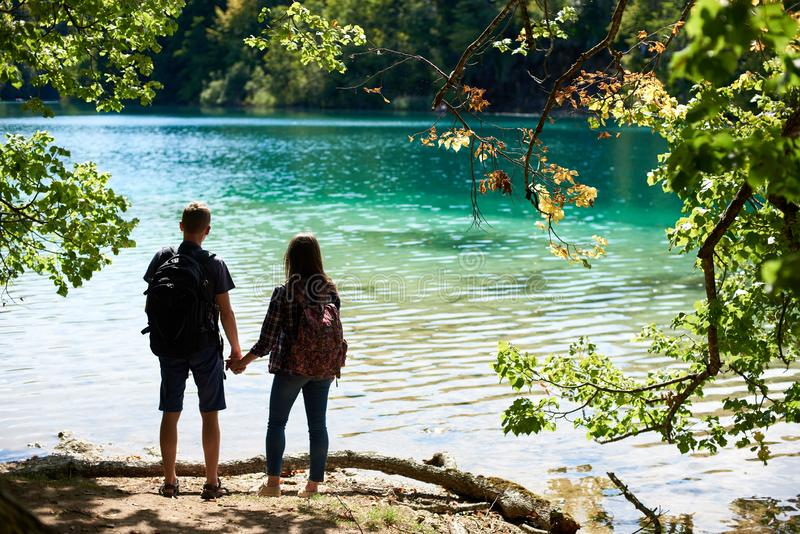 Back view of tourist couple boy and girl with backpacks standing on river bank stock photo