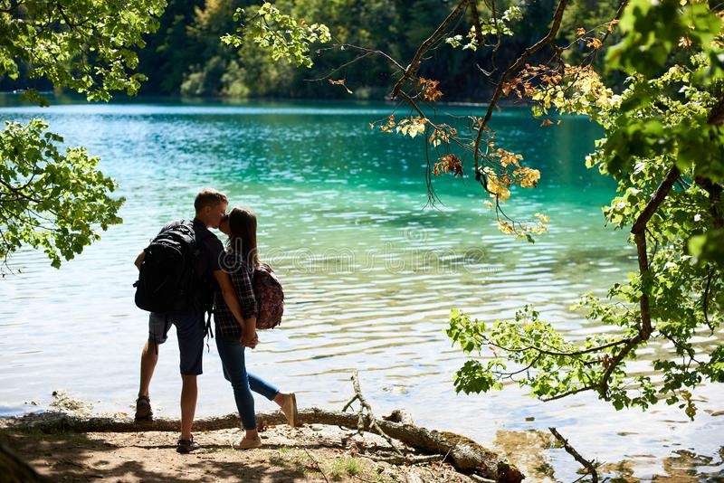 Back view of tourist couple boy and girl with backpacks standing on river bank royalty free stock photography