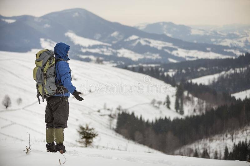 Back view of tourist hiker in warm clothing with backpack standing on mountain clearing on copy space background of woody mountain. Ridge and cloudy sky stock images