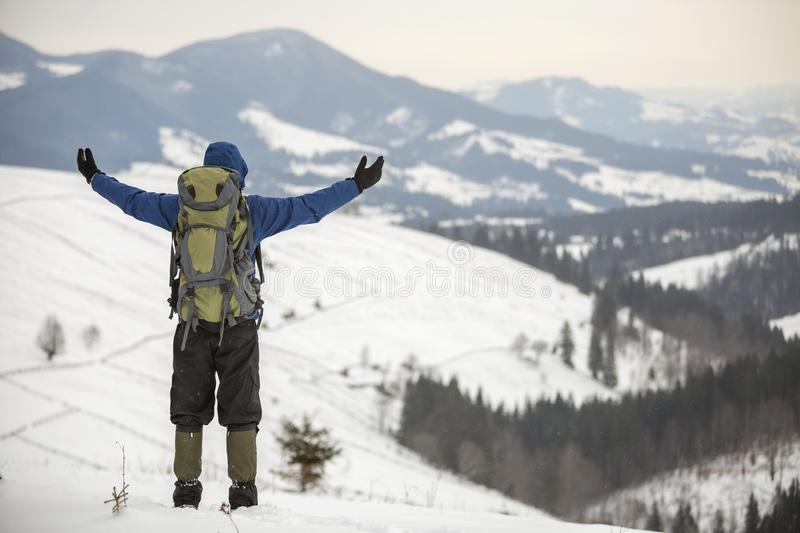 Back view of tourist hiker in warm clothing with backpack standing with raised arms on mountain clearing on copy space background royalty free stock images