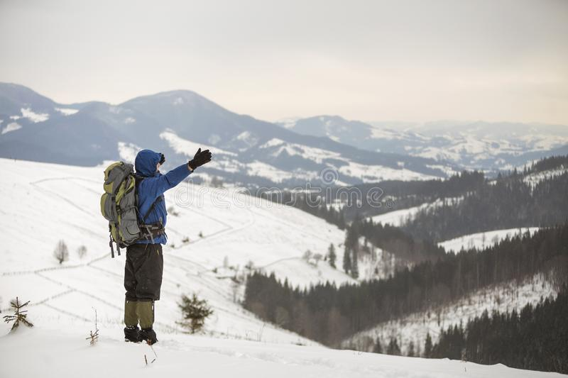 Back view of tourist hiker in warm clothing with backpack standing with raised arms on mountain clearing on copy space background stock photos