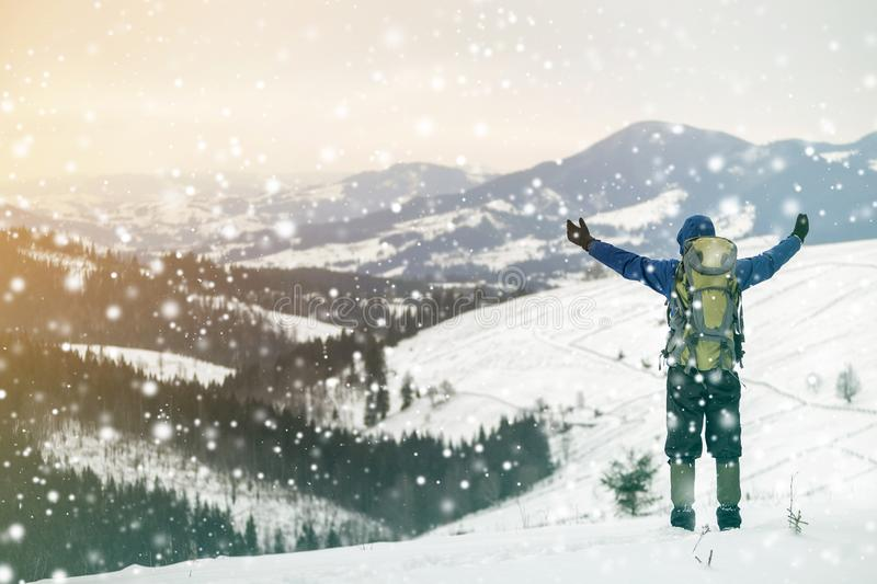 Back view of tourist hiker in warm clothing with backpack standing with raised arms on mountain clearing on copy space background. Of woody mountain ridge and royalty free stock photos