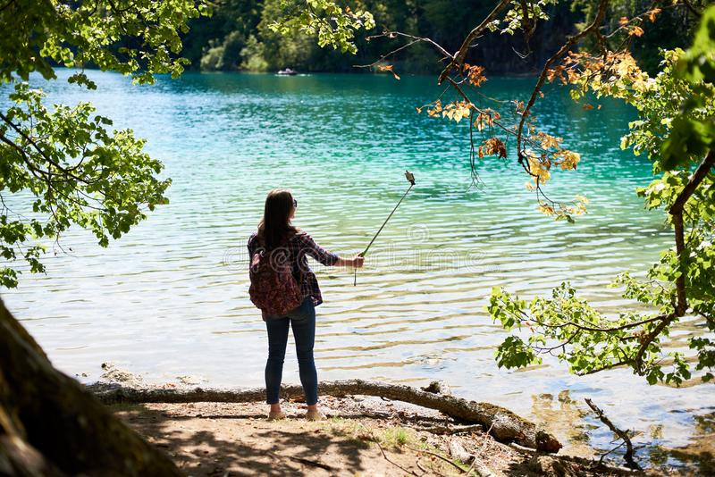 Back view of tourist woman with backpack standing on lake shore taking picture stock photo