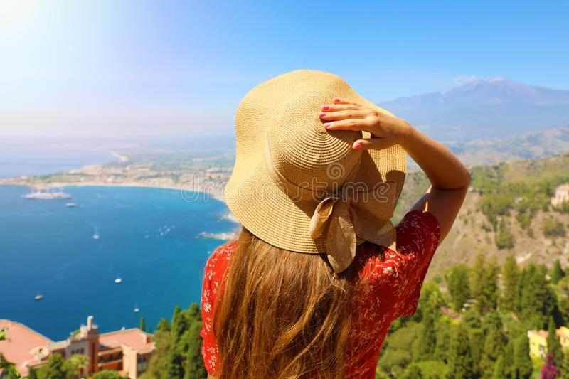 Back view of tourist woman with hat enjoying sicilian landscape view from Taormina town in Sicily, Italy stock photo