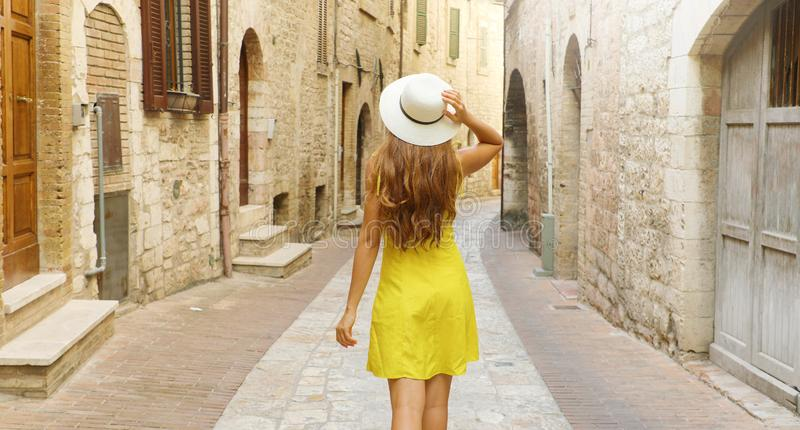 Back view of tourist woman holding hat and walking in typical medieval Tuscany street in Italy. Panoramic banner view stock image