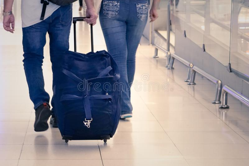 Back view of travel luggage hold on passenger hand at airport royalty free stock photography